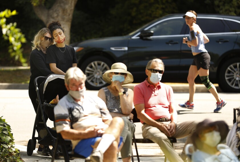 A socially distanced and mask-wearing crowd gathers on a lawn in Pasadena.