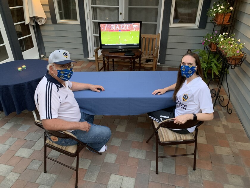 Galaxy season-ticket holder Cary Hall watches the team play Real Salt Lake with his daughter, Sarah Hall, at his home.