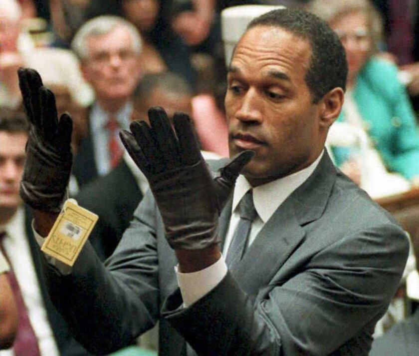 This Nov. 30, 1995, file photo shows former football player and actor O.J. Simpson looking at a new pair of Aris extra-large gloves that prosecutors had him put on during his double-murder trial in Los Angeles.