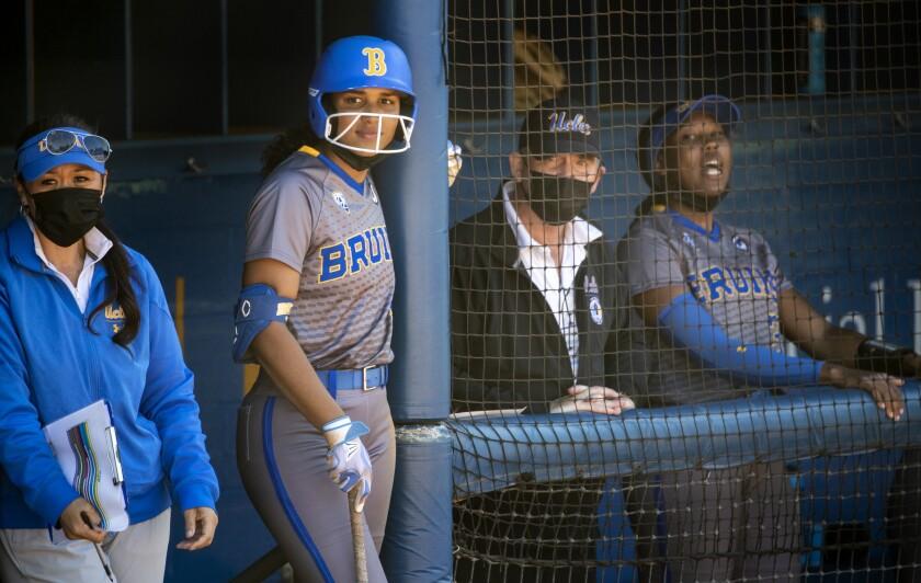 Maya Brady holds a bat outside the UCLA dugout next to head coach Kelly Inouye-Perez