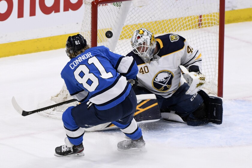 Winnipeg Jets' Kyle Connor (81) scores on Buffalo Sabres goaltender Carter Hutton (40) during the first period of an NHL hockey game, Tuesday, March 3, 2020 in Winnipeg, Manitoba. (Fred Greenslade/The Canadian Press via AP)