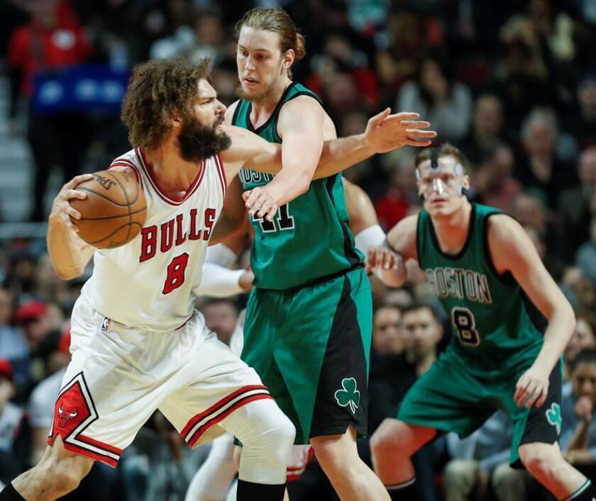 Robin López (i) de Bulls protege el balón ante Kelly Olynyk (c) de Celtics, durante el juego de la NBA en el United Center en Chicago, Illinois (EE.UU.). EPA