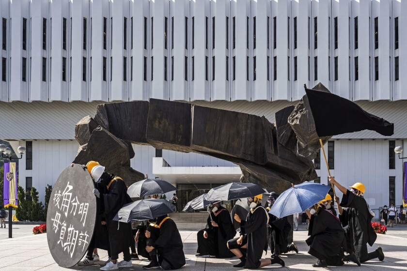 Students wearing black graduation gowns, helmets and masks protested at the Chinese University of Hong Kong in November.