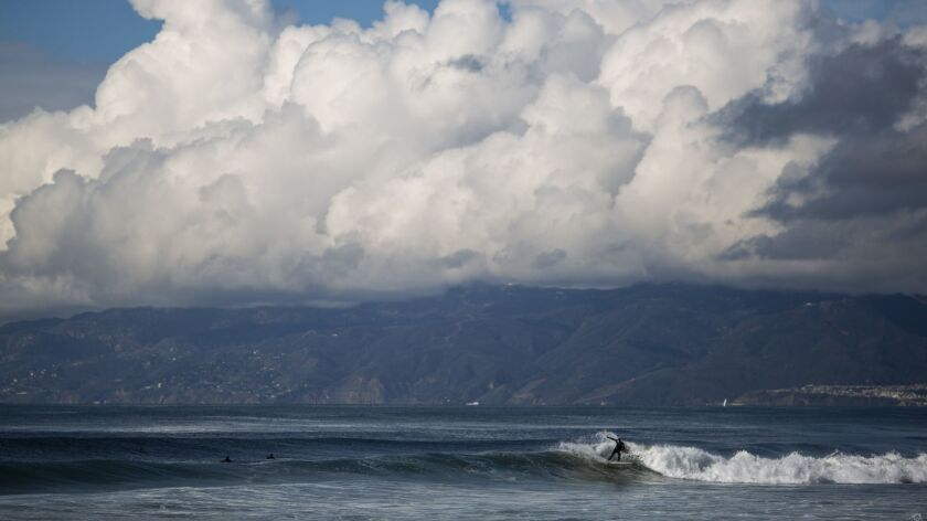 EL SEGUNDO, CALIF. - JANUARY 12: A surfer catches a wave as clouds hang over the Santa Monica mounta