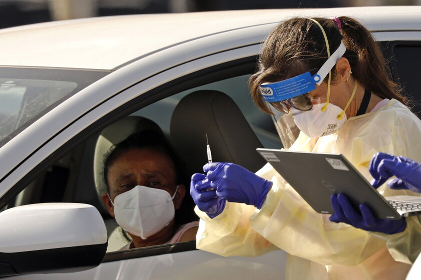 A healthworker in PPE prepares a vaccine for a motorist in a car.