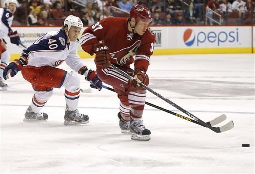 Columbus Blue Jackets' Jared Boll (40) and Phoenix Coyotes' Raffi Torres (37) battle for the puck during the first period of an NHL hockey game, Saturday, Feb. 16, 2013, in Glendale, Ariz. (AP Photo/Matt York)
