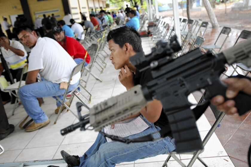 """Members of """"self-defense"""" groups wait to register their weapons in Apatzingan, Mexico, before a federally imposed deadline."""