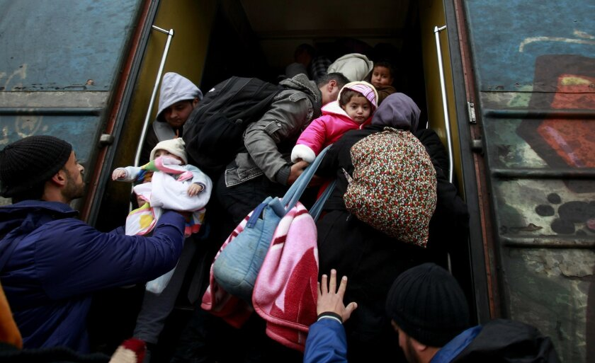 Refugees rush to board a train before its departure towards Serbia, from the transit center for refugees near the southern Macedonia's town of Gevgelija, Sunday, Feb. 14, 2016. Dutch foreign minister Bert Koenders has urged on Sunday some EU member states not to close their borders for migrants, su