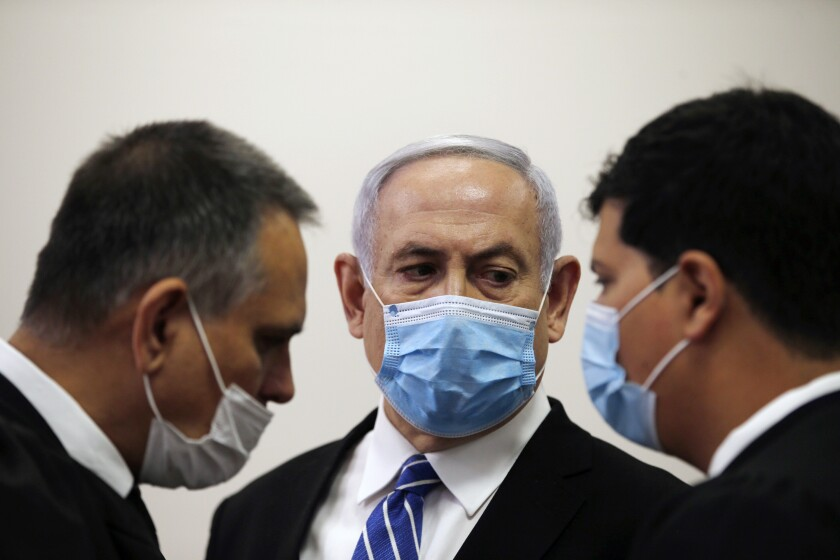 Israeli Prime Minister Benjamin Netanyahu, wearing a face mask in line with public health restrictions due to the coronavirus pandemic, looks at his lawyer inside the court room as his corruption trial opens at the Jerusalem District Court, Sunday, May 24, 2020. He is the country's first sitting prime minister ever to go on trial, facing charges of fraud, breach of trust, and accepting bribes in a series of corruption cases stemming from ties to wealthy friends. (Ronen Zvulun/ Pool Photo via AP)