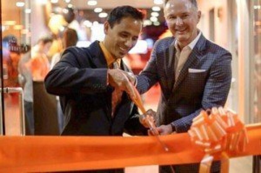 Billy Borja cuts the ribbon with business partner, Brian Ahern. Courtesy