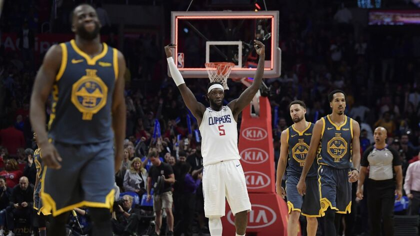 Clippers forward Montrezl Harrell, center, celebrates as time runs out in overtime as Golden State Warriors forward Draymond Green, left, guard Klay Thompson, second from right, and guard Shaun Livingston walk off the court.