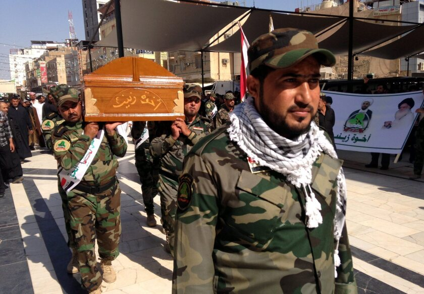 Members of Asaib Ahl Al-Haq, an Iraqi Shiite militia, carry the coffin of a comrade killed in clashes with Sunni gunmen near Tikrit, Iraq, during a funeral procession in Najaf, on Sunday.
