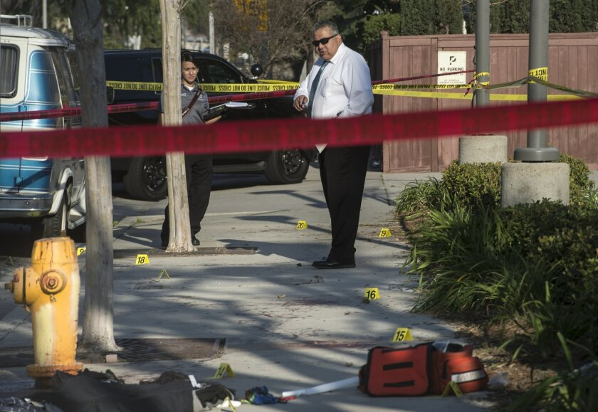 Detective J.D Duran, right, and Anaheim Police Department forensics officerJeannette Torres investigate the scene in Anaheim, Calif., Saturday, Feb.27, 2016, after a small group of Ku Klux Klan members staging an anti-immigrant rally clashed with a larger gathering of counter-protesters, police said. Three people were stabbed Saturday, one critically, during the clash. (Ed Crisostomo/The Orange County Register via AP) MAGS OUT; LOS ANGELES TIMES OUT; MANDATORY CREDIT Photo by ED CRISOSTOMO, THE ORANGE COUNTY REGISTER