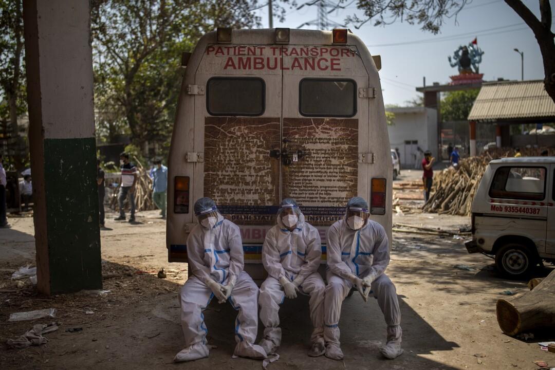 Three men sit beside an ambulance.