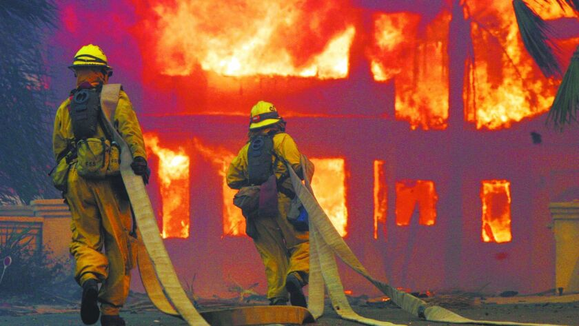 Firefighters battle in Poway during the 2007 wildfires that destroyed more than 1,300 homes.