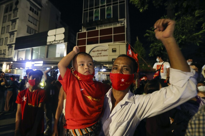Supporters in face masks cheer in front of Myanmar leader Aung San Suu Kyi's National League for Democracy headquarters.