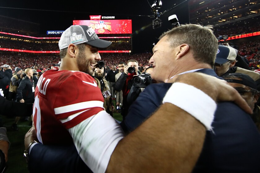 Jimmy Garoppolo of the San Francisco 49ers  hugs general manager John Lynch after winning the NFC Championship game against the Green Bay Packers at Levi's Stadium.