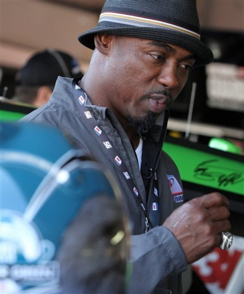 Former Philadelphia Eagles safety Brian Dawkins, grand marshal for the race, stands in a garage before the NASCAR Sprint Cup Series auto race Sunday, Sept. 30, 2012, at Dover International Speedway in Dover, Del. (AP Photo/The News-Journal, Daniel Sato) NO SALES