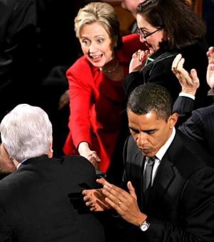 Sen. Hillary Rodham Clinton greets Sen. Edward Kennedy, back to camera, as Sen. Barack Obama turns away before President Bush's State of the Union address in Washington.