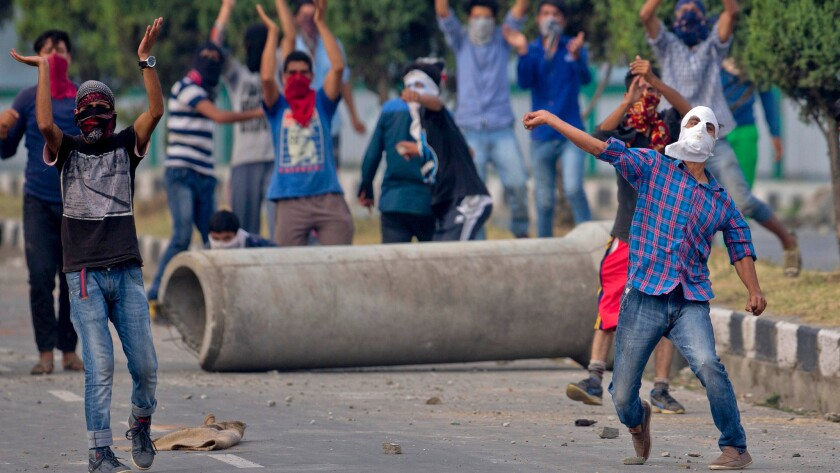A protester throws stones during clashes with Indian troops in Srinagar, Indian-administered Kashmir, on July 12.