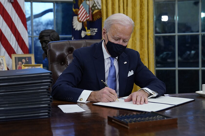 President Biden signs his first executive orders in the Oval Office on Jan. 20.
