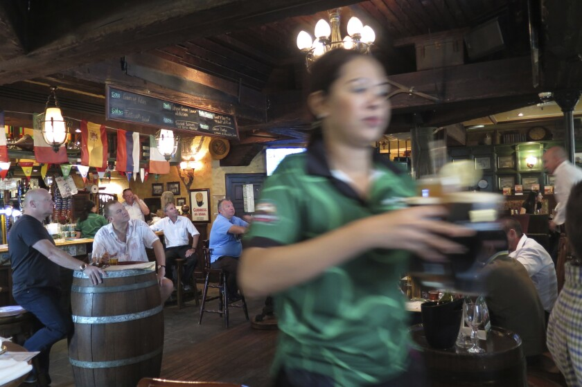 FILE - In this June 22, 2016 file photo, a waitress serves customers beer at a restaurant in Dubai, United Arab Emirates. In mid-September 2020, Abu Dhabi, the conservative capital of the United Arab Emirates, eliminated its licensing system for alcohol purchases allowing Muslims previously barred from obtaining licenses to be able to purchase from retailers. (AP Photo/Kamran Jebreili, File)