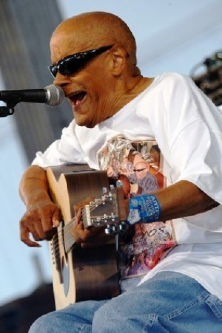 Musician Snooks Eaglin, here performing at last year's New Orleans Jazz and Heritage Festival, had an unusual playing style: He'd pick guitar strings with his thumbnail.