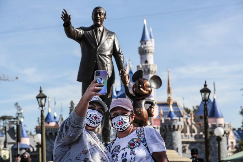 Visitantes enmascarados se toman un selfie frente a una estatua de Walt Disney y Mickey Mouse en Disneylandia.
