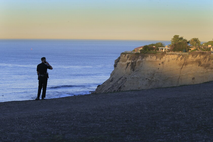 A Palos Verdes Estates police officer watches for trouble from the bluff above Lunada Bay.