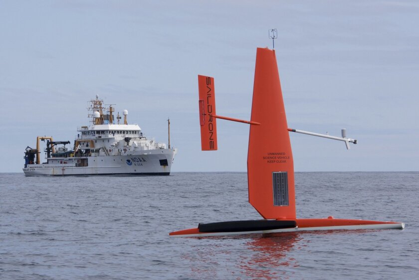 In this April 2015 photo released by NOAA Fisheries, a Saildrone, a 20-foot sailing vessel research platform developed by California-based Saildrone Inc., is tested in the Bering Sea. The National Oceanic and Atmospheric Administration research vessel Oscar Dyson is in the background. Two of the un