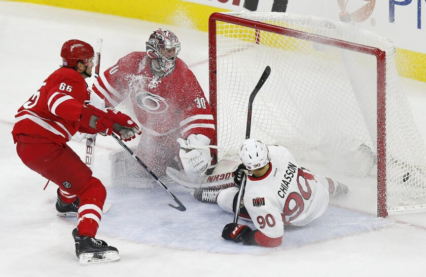 Ottawa Senators' Alex Chiasson (90) scores a second-period goal against Carolina Hurricanes goaltender Cam Ward, center, and as Hurricanes' Ron Hainsey, left, defends during an NHL hockey game in Raleigh, N.C., Saturday, Nov. 7, 2015. (AP Photo/Ellen Ozier)