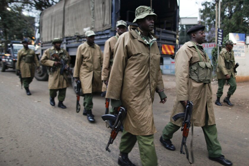 Kenyan paramilitary officers walk toward a small shopping arcade next to the Westgate shopping mall, where a hostage situation continued in Nairobi, Kenya, on Sunday.