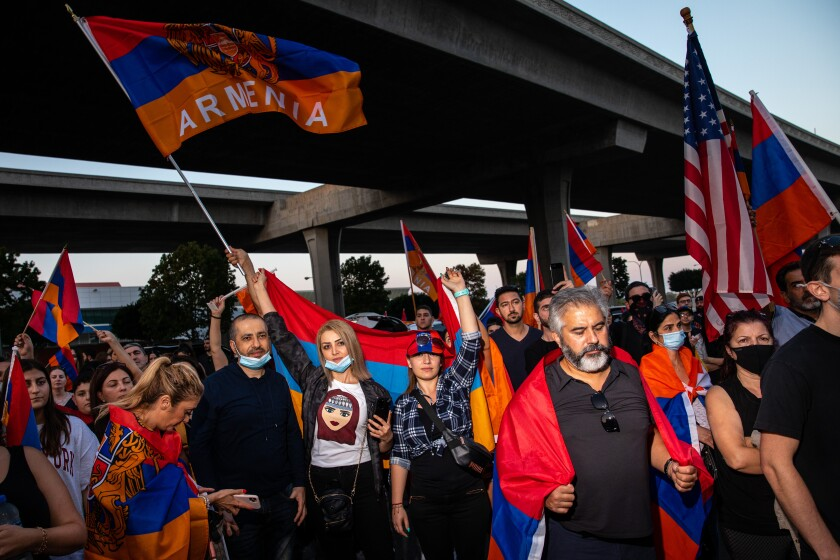 People waving Armenian flags and wearing the red orange and blue colors protest near a freeway overpass