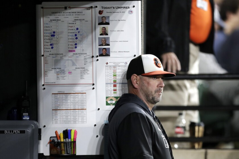 FILE - In this Sept. 19, 2019, file photo, Baltimore Orioles manager Brandon Hyde watches from the dugout during the seventh inning of a baseball game against the Toronto Blue Jays in Baltimore. Hyde enters his second spring training as manager of the Baltimore Orioles with the same goal as last year: to oversee the rebuild of a last-place team that lost more than 100 games. (AP Photo/Julio Cortez, File)