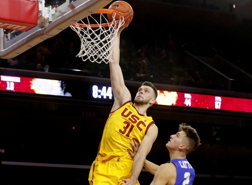 USC forward Nick Rakocevic dunks over Florida Gulf Coast guard Caleb Catto.
