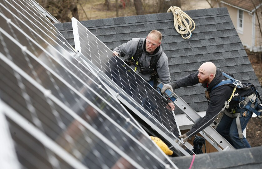 Edward Carrico and Spencer Kearney, with Solar Service in Niles, Ill., install solar panels on a home on Tuesday, March 28, 2017 in Lake Zurich, Ill.