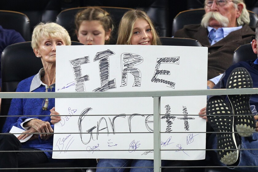 """A fan holds a sign that reads """"Fire Garrett"""" in the fourth quarter of a game between the Dallas Cowboys and the Buffalo Bills on Nov. 28 in Arlington, Texas."""