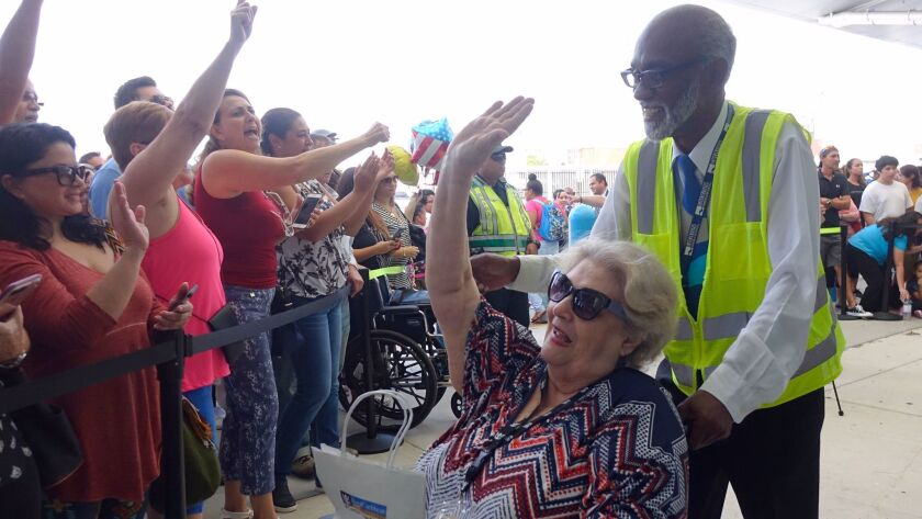 A crowd greets Caribbean hurricane evacuees arriving in Fort Lauderdale, Fla., aboard the Royal Caribbean Adventure of the Seas.