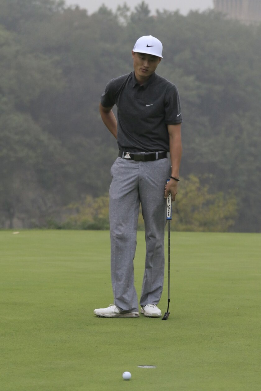 Li Haotong of China reacts after missing a putt on the 17th hole during the third round of the HSBC Champions golf tournament at the Sheshan International Golf Club in Shanghai, China Saturday, Nov. 7, 2015. (AP Photo)