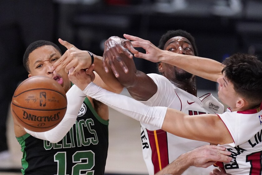 Boston Celtics' Grant Williams (12) fights for the ball with Miami Heat's Bam Adebayo, center, and Tyler Herro, right, during the second half of an NBA conference final playoff basketball game Friday, Sept. 25, 2020, in Lake Buena Vista, Fla. (AP Photo/Mark J. Terrill)