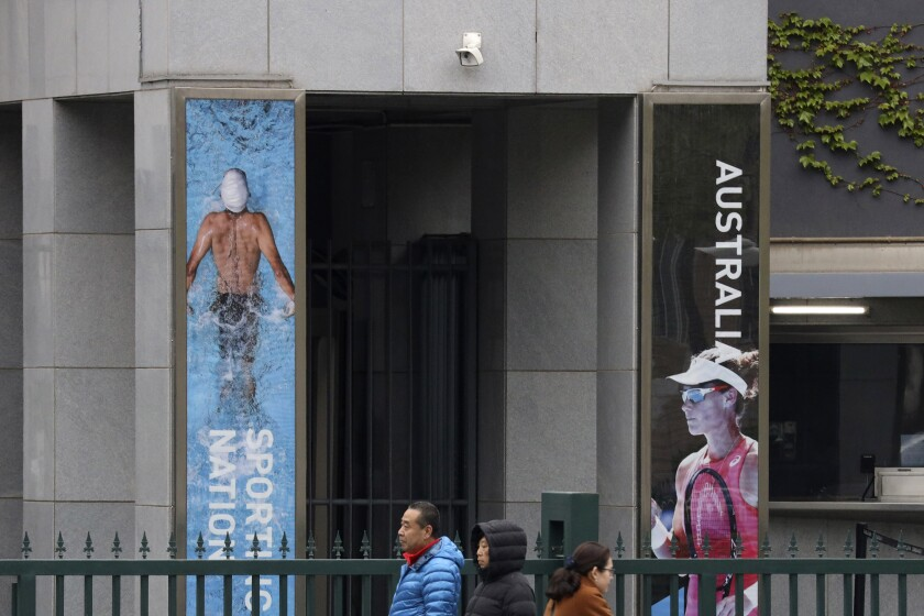 Residents walk pas the Australian embassy in Beijing, China April 9, 2019. In a notice issued June 5, 2020, China is advising its citizens not to visit Australia, citing racial discrimination and violence against Asians, in what appears to be Beijing's latest attempt to punish the country for advocating an investigation into the coronavirus pandemic. (AP Photo/Ng Han Guan)