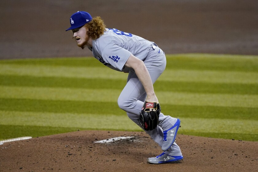 Dodgers starting pitcher Dustin May gets up after taking a comebacker off his foot.