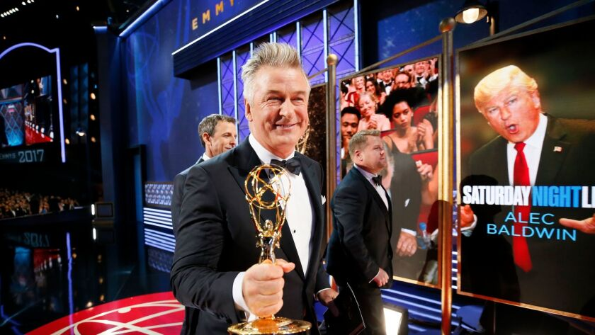 """A happy Alec Baldwin shows off his Emmy for supporting actor in a comedy for his work on """"Saturday Night Live,"""" backstage at the Primetime Emmy Awards on Sunday."""