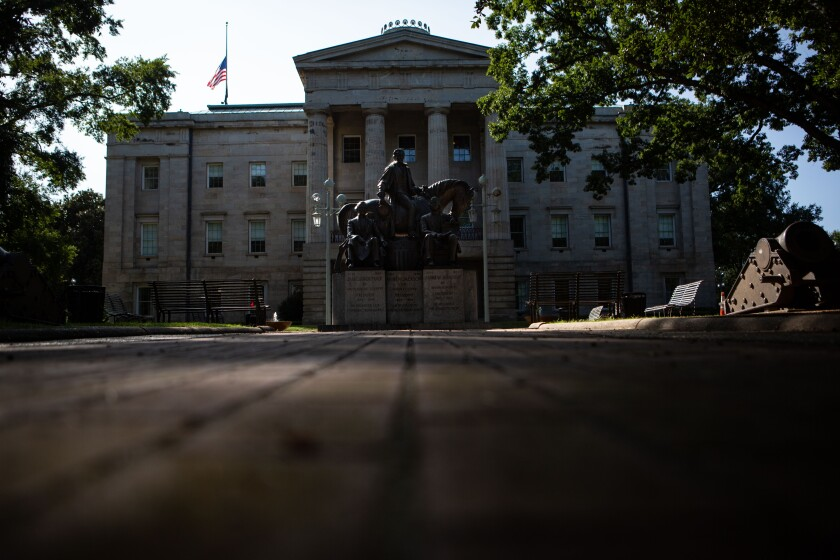 An exterior view of the North Carolina Capitol with a statue of a man on a horse.