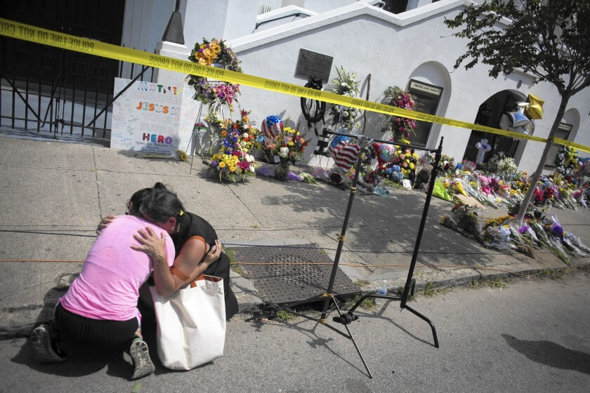 Women mourn at the memorial site outside the Emanuel AME Church, where nine people were killed Wednesday in Charleston, S.C.