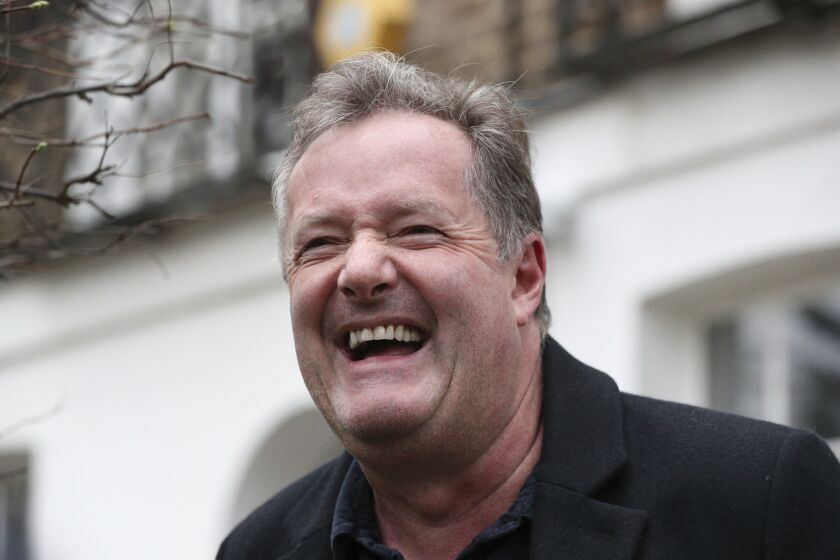 """British television host Piers Morgan laughs as he speaks to reporters outside his home in Kensington, central London, Wednesday March 10, 2021. Morgan quit the """"Good Morning Britain"""" program on Tuesday after making controversial comments about the Duchess of Sussex. The U.K.'s media watchdog said earlier Tuesday it was launching an investigation into the show under its harm and offense rules after receiving more than 41,000 complaints about Morgan's comments on Meghan. (Jonathan Brady/PA via AP)"""