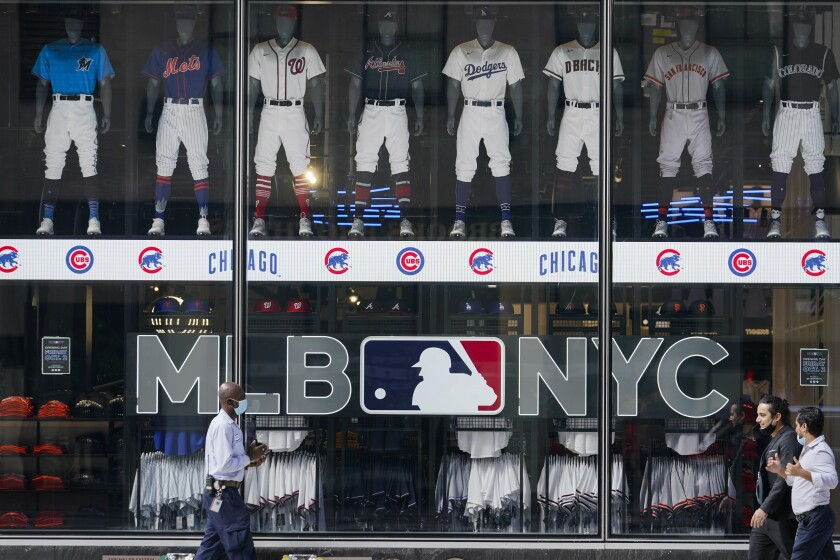 Pedestrians pass the MLB Flagship store Wednesday, Sept. 30, 2020, in New York. The two-floor store is in the space formerly occupied by the studio of the New York Mets' SNY regional sports network. (AP Photo/Frank Franklin II)