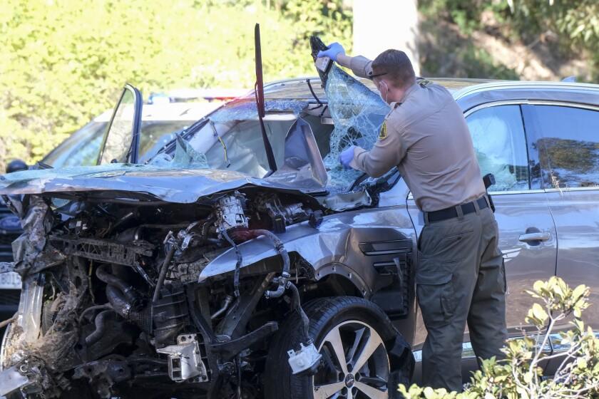 un agente policial observa el vehículo en que se accidentó el golfista Tiger Woods,