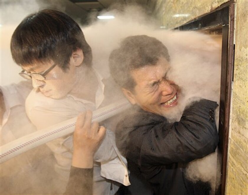 South Korean opposition Democratic Party members try to enter into a parliamentary committee room as ruling Grand National Party members, not in photo, spray fire extinguishers from the room, to block them at the National Assembly in Seoul, South Korea, Thursday, Dec. 18, 2008. Scuffles erupted in the South Korean parliament Thursday as opposition parties tried to block a ruling party move to introduce a bill to approve a free trade pact with the United States.(AP Photo/Yonhap, Kim Ju-seong)