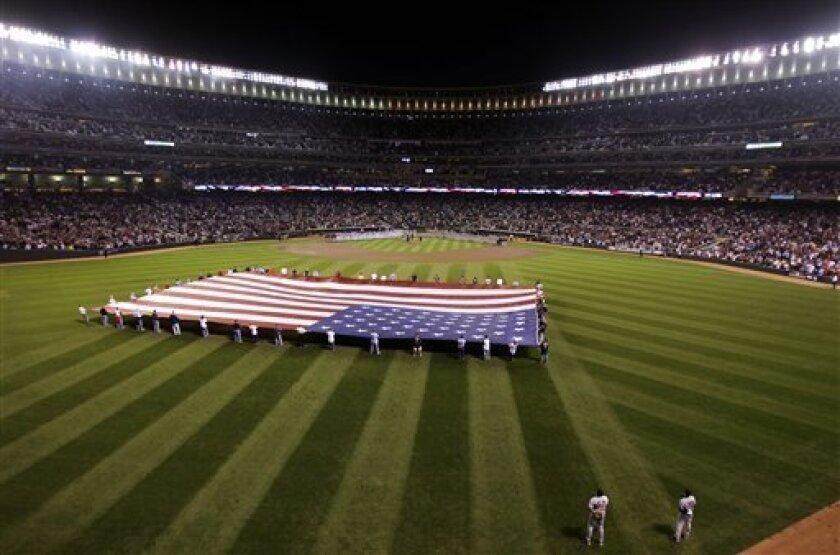 A large U.S. flag is held in center field before Game 1 of baseball's American League Division Series between the Minnesota Twins and the New York Yankees on Wednesday, Oct. 6, 2010, in Minneapolis. (AP Photo/Paul Battaglia)